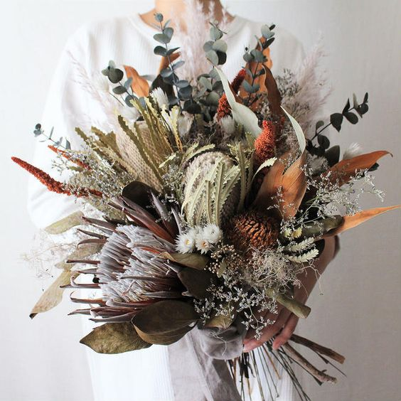 an oversized wedding bouquet with dried blooms and foliage, fresh greenery and blooms shows off much texture