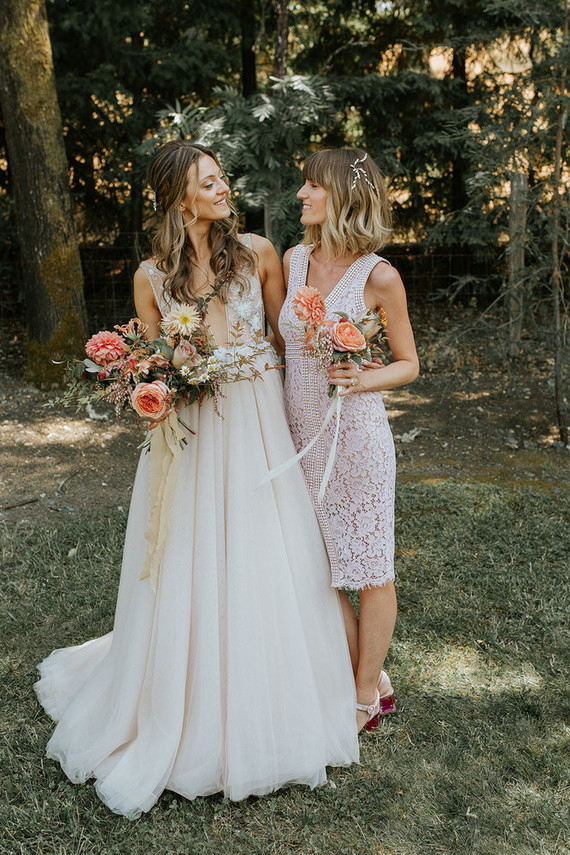 The bride was wearing a neutral plunging neckline wedding dress with floral appliques, a full skirt plus a wavy half updo
