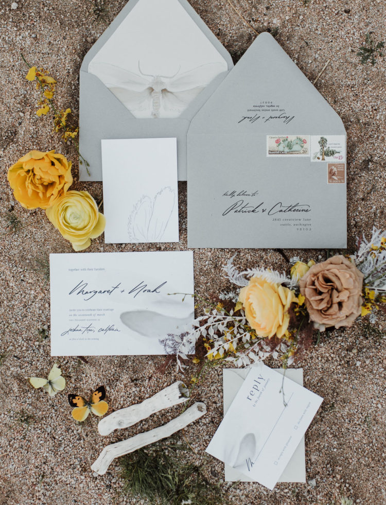 The wedding invitation suite was done in grey and white, with black calligraphy and insect prints