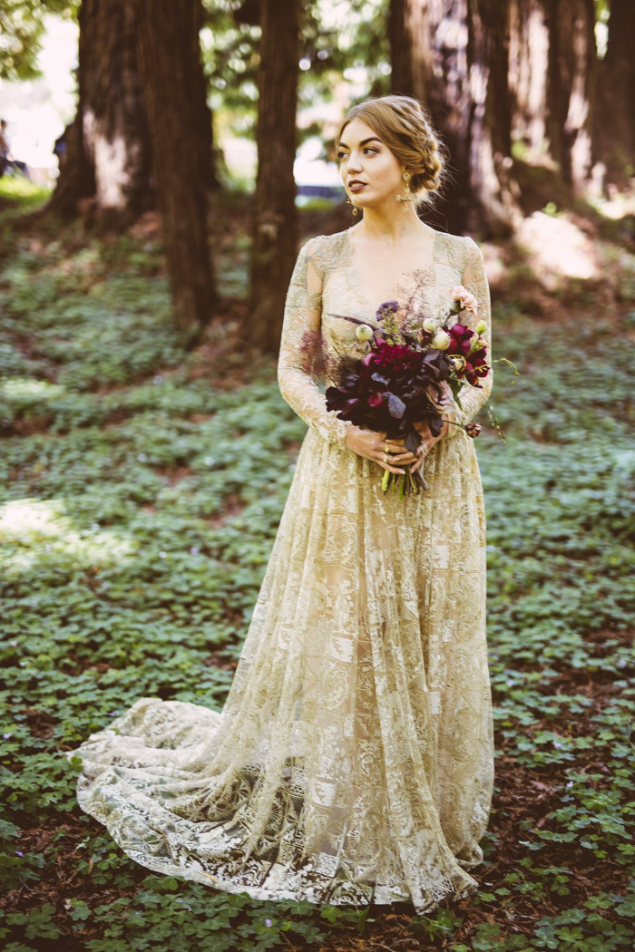 a beautiful gold lace wedding gown with a train, long sleeves and a V-neckline is a chic option for a forest bride