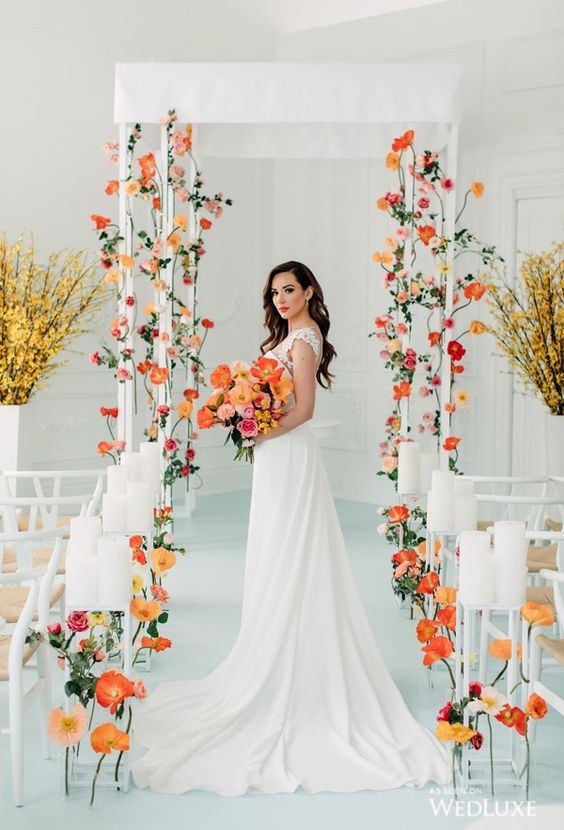 a bright modern wedding aisle done with white chairs, colorful blooms in orange and rust, candles on tall stands