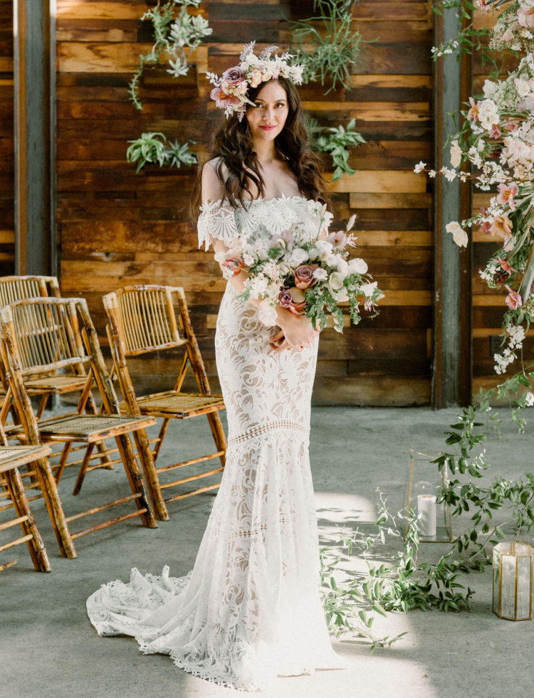 The bride was wearing a beautiful off the shoulder boho lace wedding dress and a lush blush floral crown
