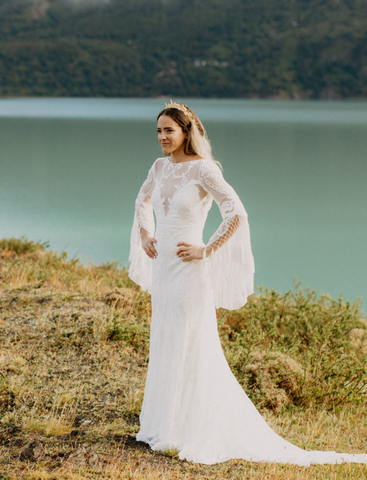 The bride was wearing a boho lace mermaid wedding dress with bell sleeves and tassels and a train by Rue De Seine