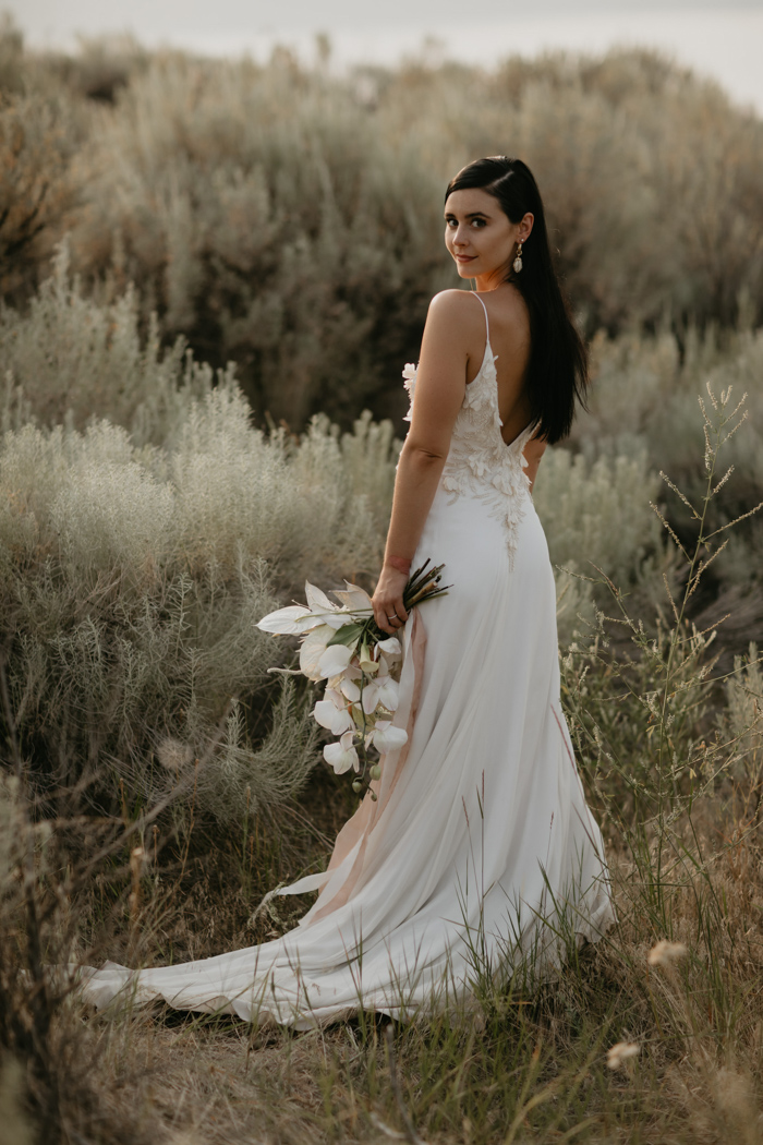 The bride was wearing a modern spaghetti strap wedding dress with appliques, a cutout back and a train