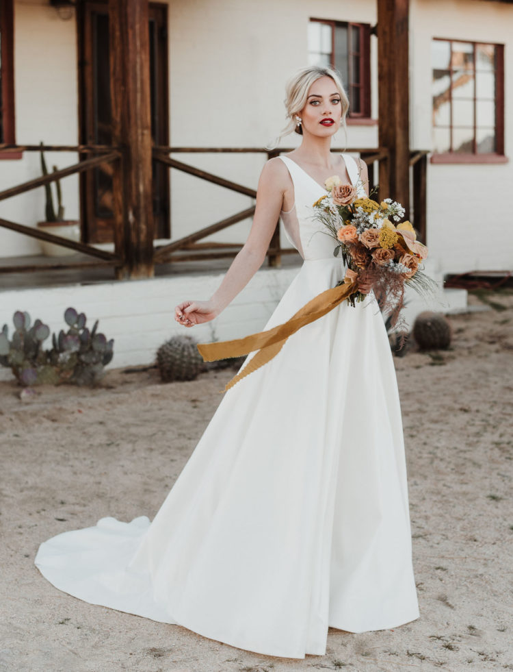 The bride was wearing a stunning minimalist wedding gown with a plunging neckline and sheer inserts on the sides