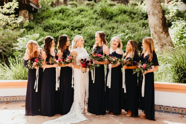 The bridesmaids were wearing mismatching black maxi dresses and carrying bright bouquets