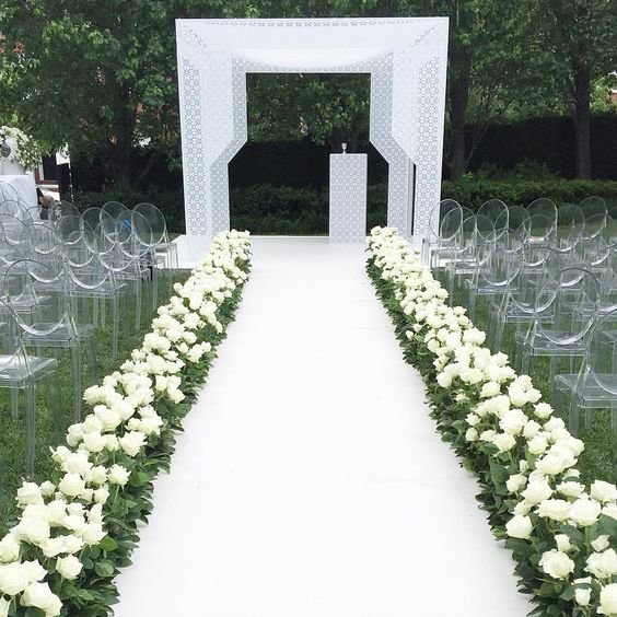 a luxurious modern wedding aisle with a white runner, fresh white roses, ghost chairs and a matching white geometric arch