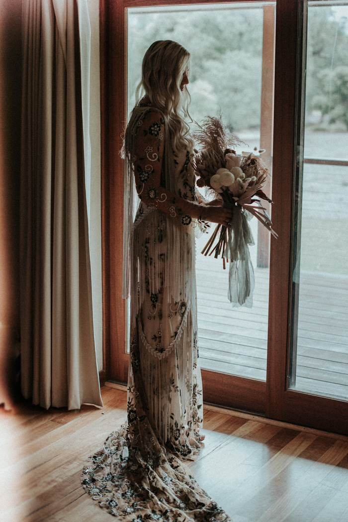 The bride was wearing a neutral wedding dress by Rue De Seine with colorful botanical embroidery and super long fringe