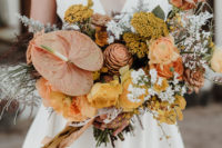 04 The fantastic wedding bouquet was done in rust, mustard and yellow shades and with pale greenery and herbs