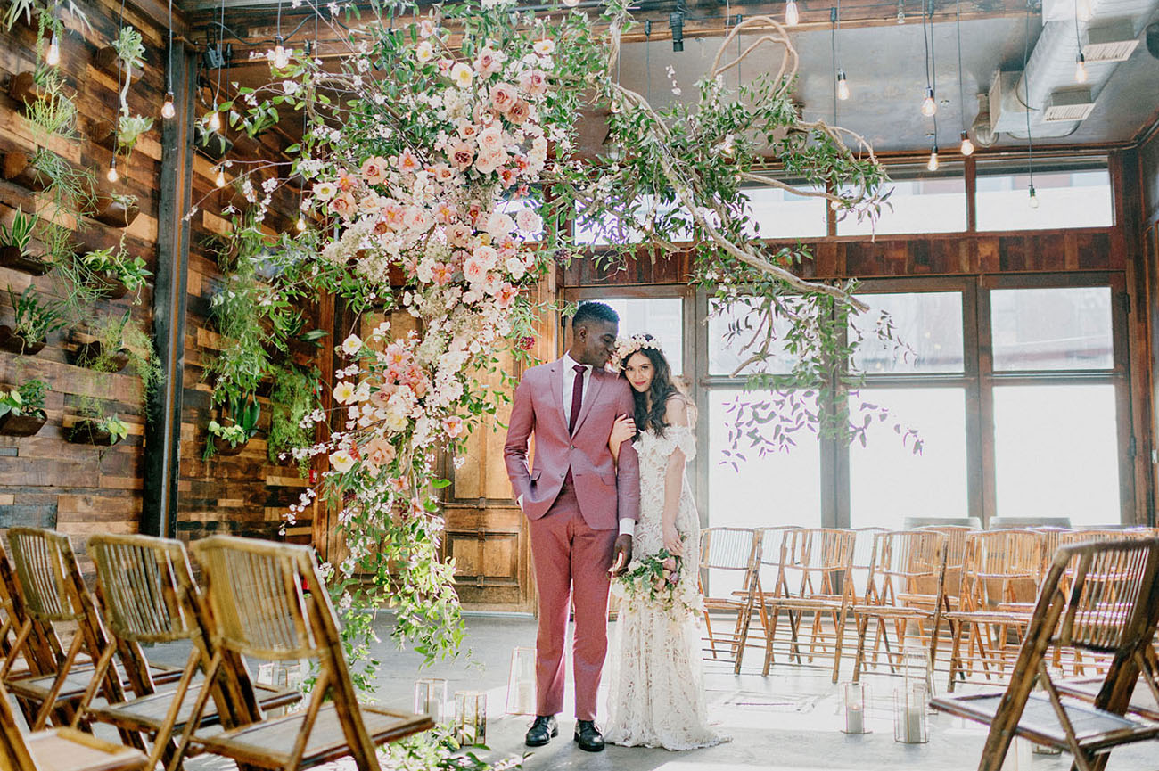 The groom was wearing a bright pink suit, a burgundy tie and black shoes