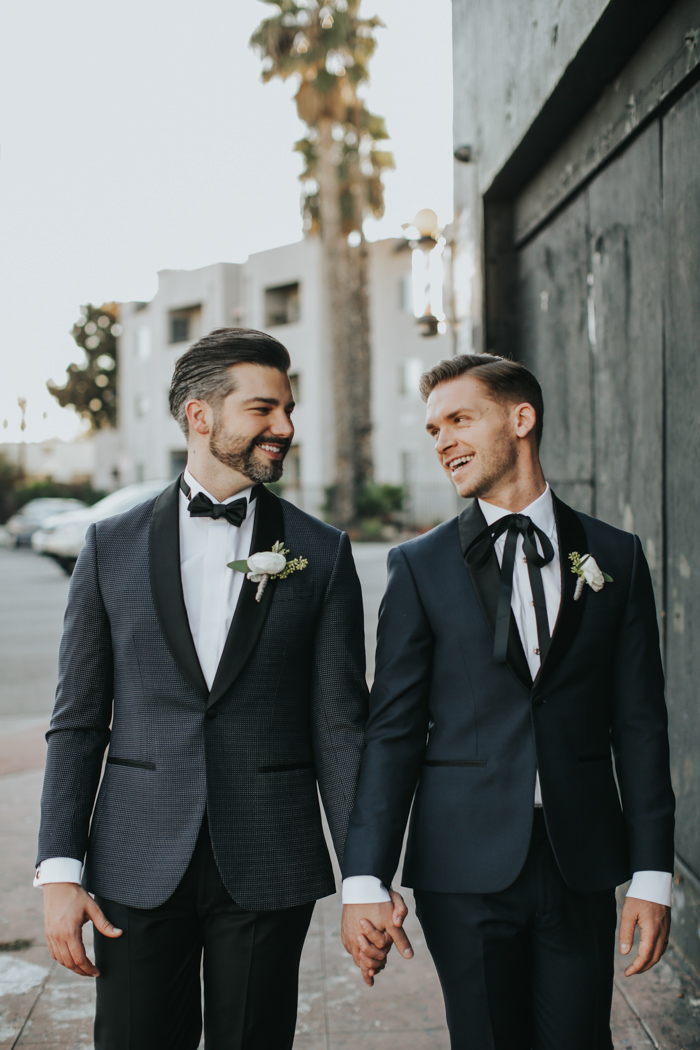 One groom preferred a navy tux with black lapels, a black bow and a white shirt, the other went for a printed black tux with black lapels and a bow tie