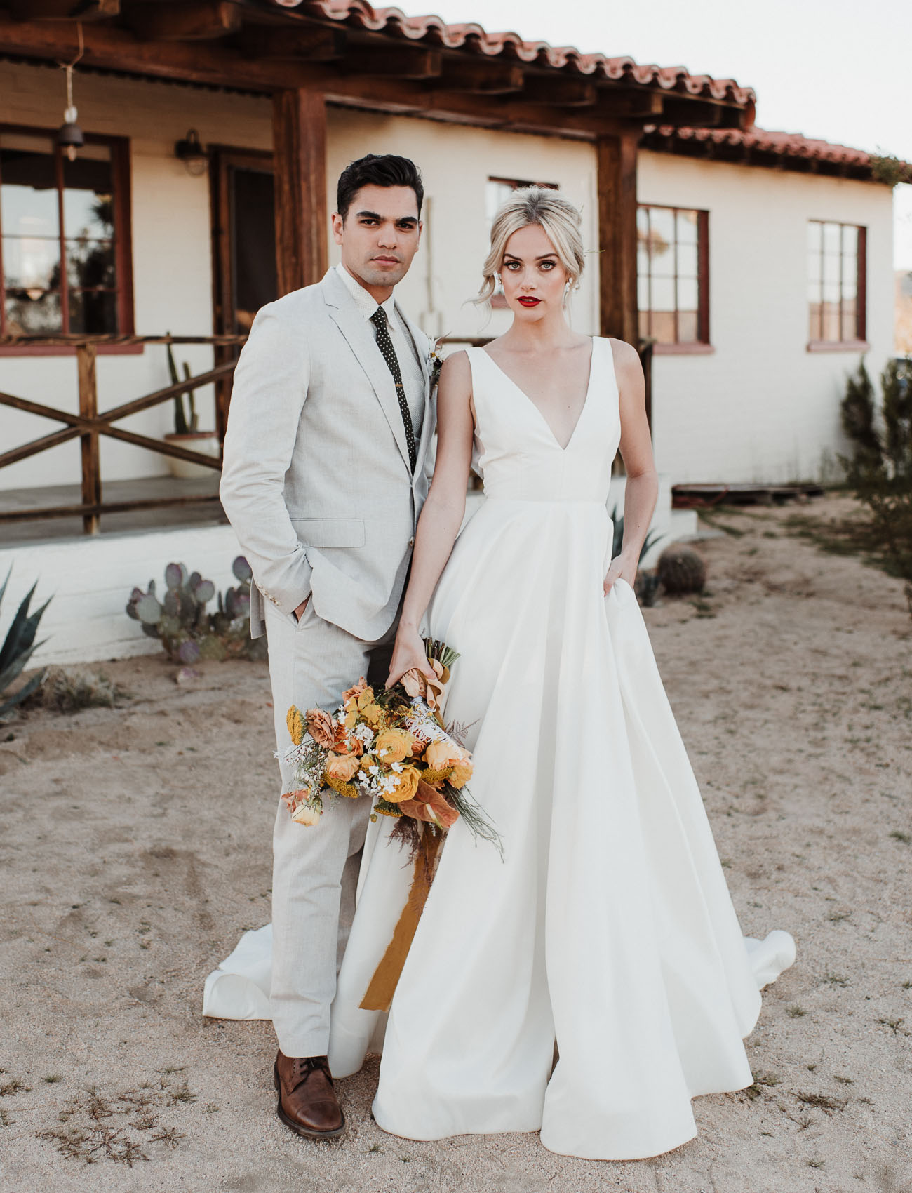 The bride's lips were red and she was rocking a wavy updo, the groom was wearing a dove grey suit with a printed tie and brown shoes