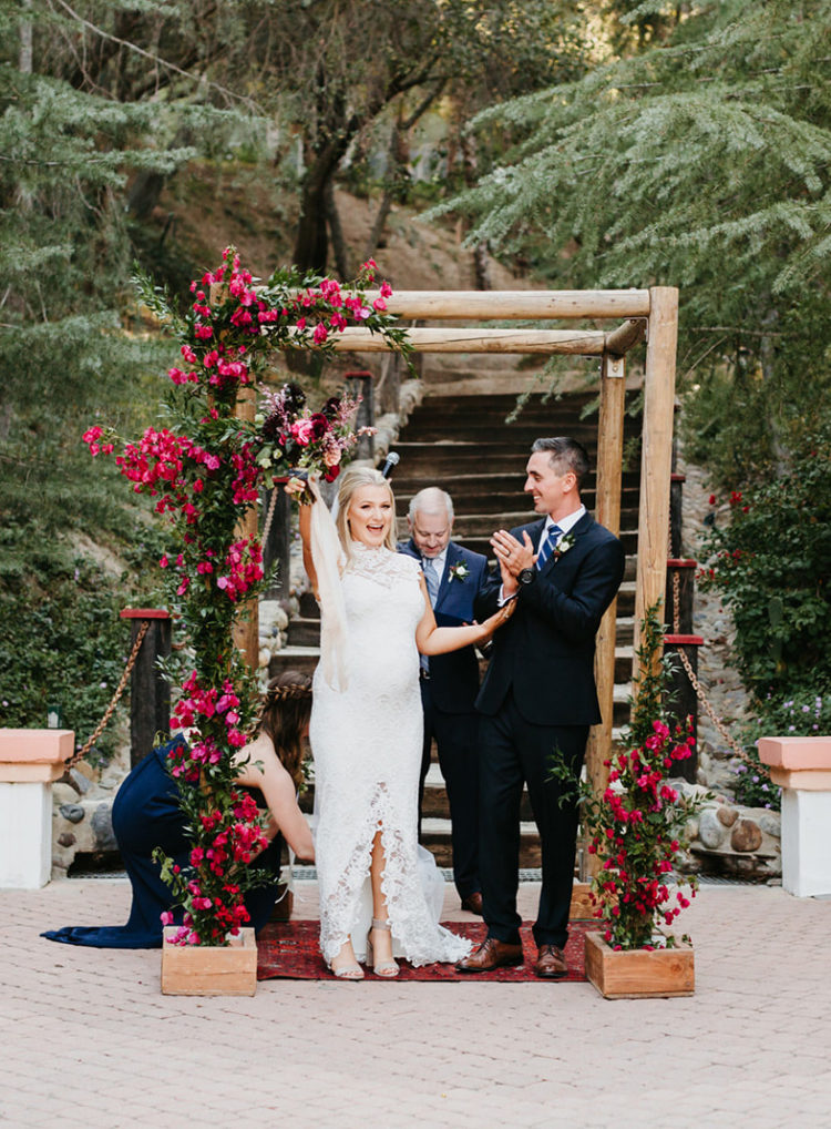 The groom was wearing a black suit with a navy tie and brown shoes, and the wedding arch was decorated with bougainvilleas