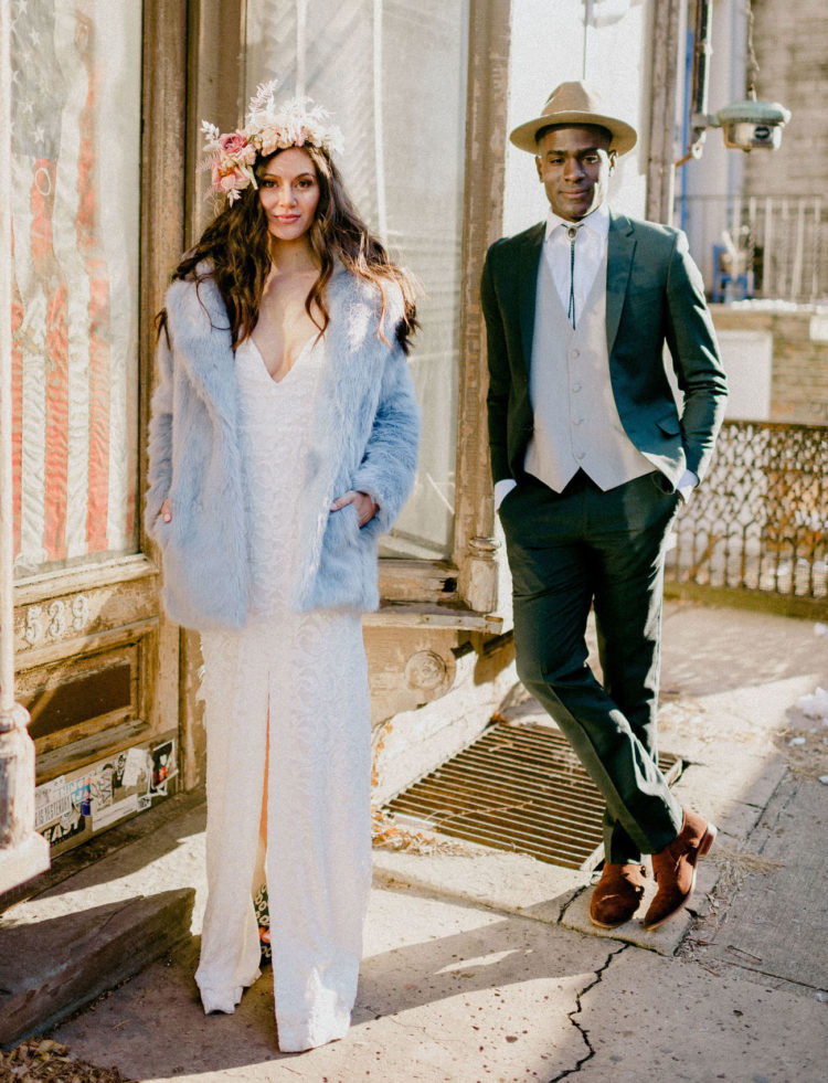 The next looks were done with a lace boho wedding dress and a blue faux fur coat and a black suit, neutral vest and a bolo tie