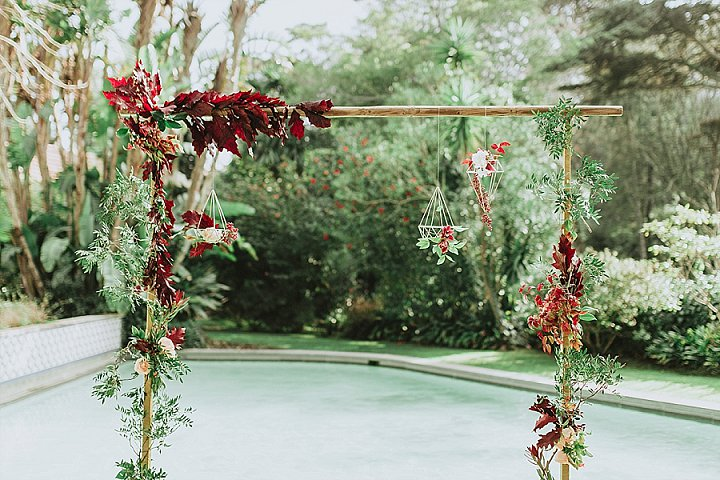 The wedding arch was done with burgundy leaves and blooms, greenery and geometric touches