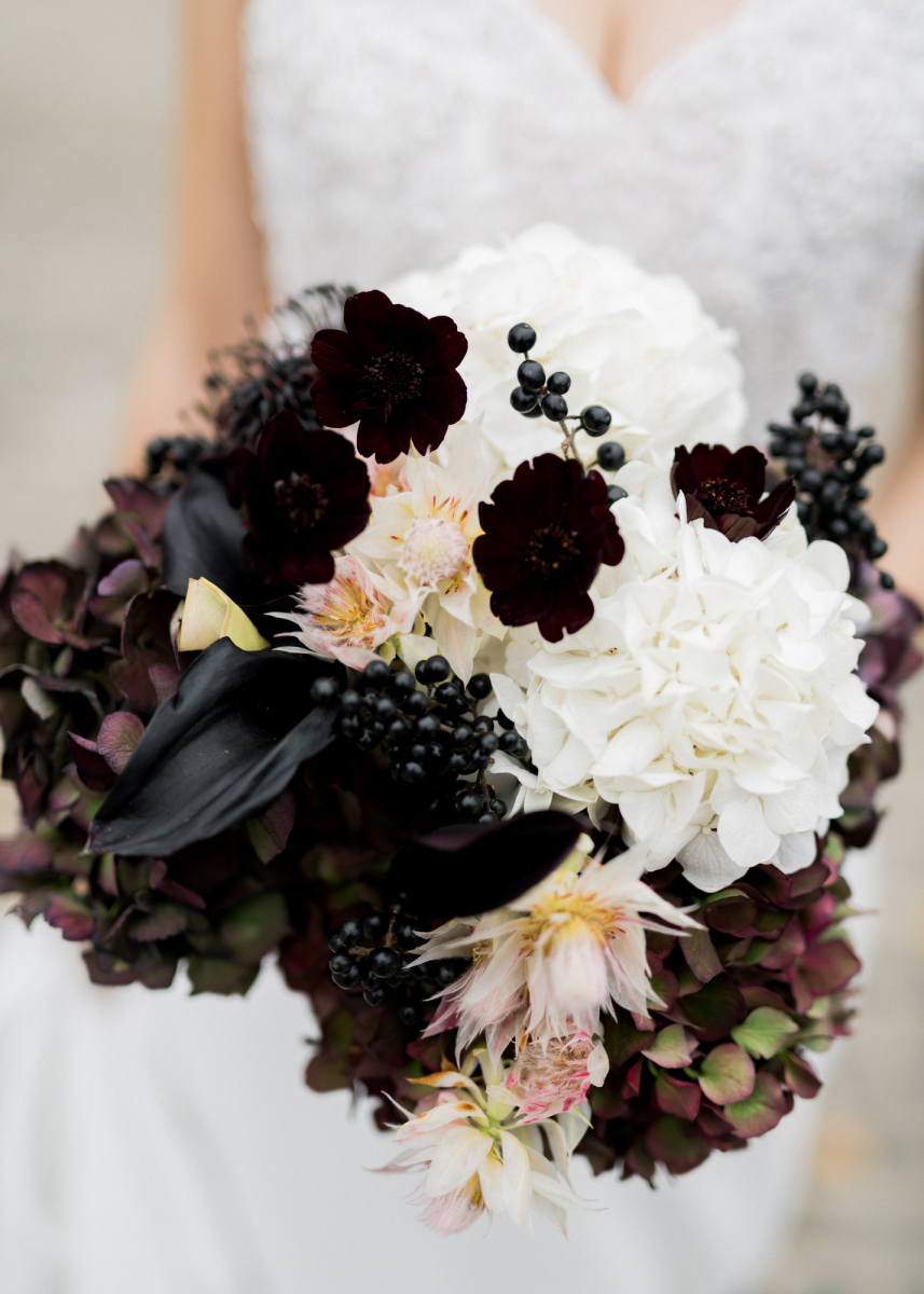 The wedding bouquet was done with black callas, berries, dark hydrangeas and white and blush blooms
