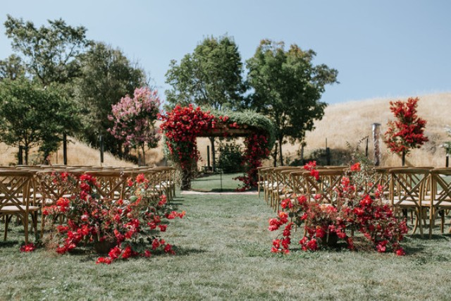The wedding ceremony space was done with bright red florals and the wedding arch was done with much greenery and bright red blooms