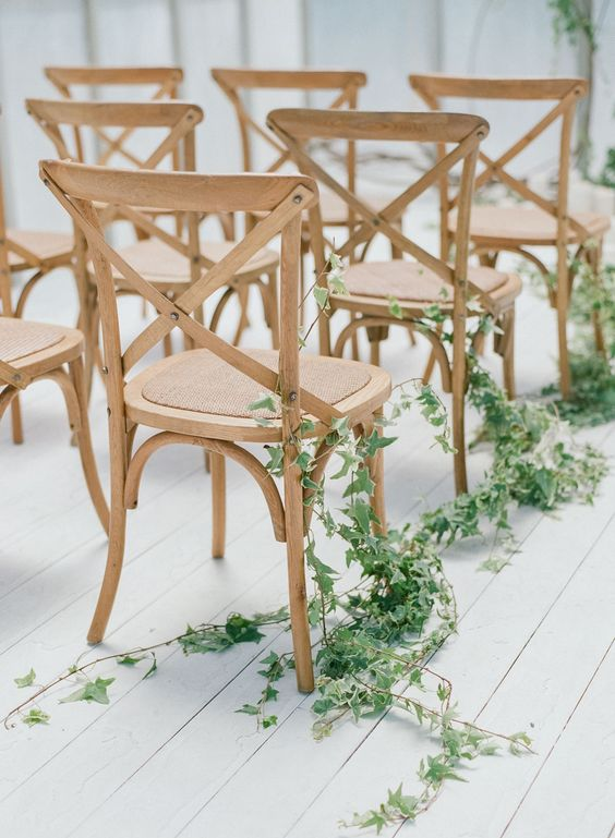 a modern wedding aisle done with simple wooden chairs and lush greenery climbing up the chairs is all you need for a cool look