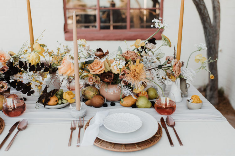 The amazing tablescape was done with lush yellow, mustard and rust blooms plus dark foliage, fresh fruits and wicker chargers