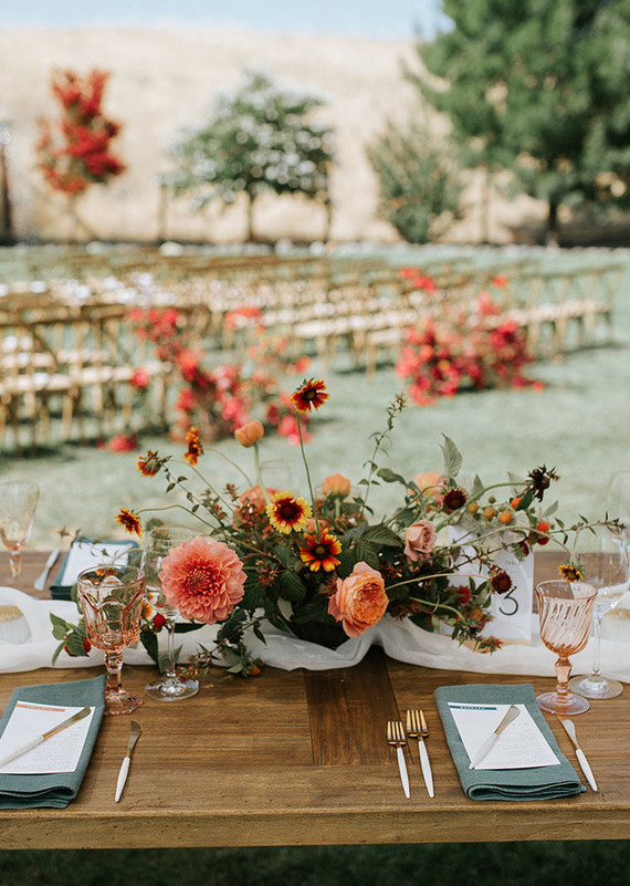 The wedding tablescape was done with rust, orange, red blooms and teal napkins