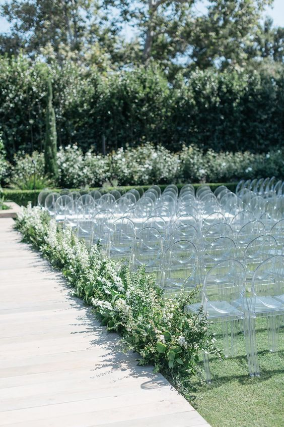 a modern wedding aisle with ghost chairs, lush greenery and white blooms all over for a chic look