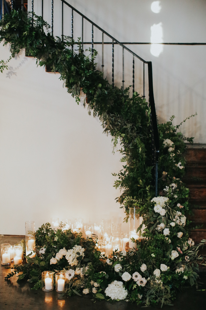 look at this gorgeous staircase decorated with lush greenery and white blooms and candles, isn't it amazing