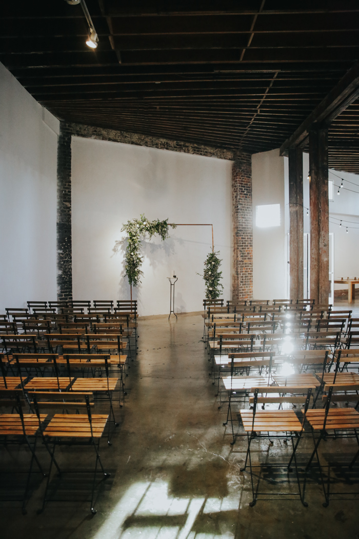The ceremony space was truly industrial, with a copper frame decorated with greenery and blooms and folded wooden chairs