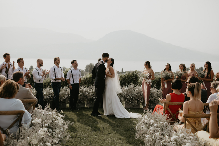 The wedding ceremony took place outdoors, with pale greenery and white blooms that also lined the aisle