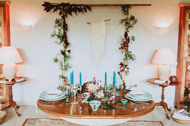 The wedding reception space was done with turquoise candles, bright blooms, geometric decor and a macrame hanging