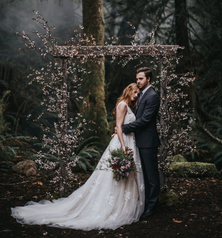 a beautiful wedding arch with blush and pink blooming branches is a chic idea for an enchanted forest wedding