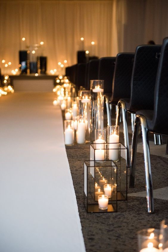 a simple and chic modern wedding aisle with black chairs, geometric lanterns and just candles on the floor
