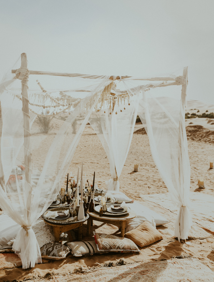 Small wooden tables, pillows and rugs helped to create a boho chic picnic setting
