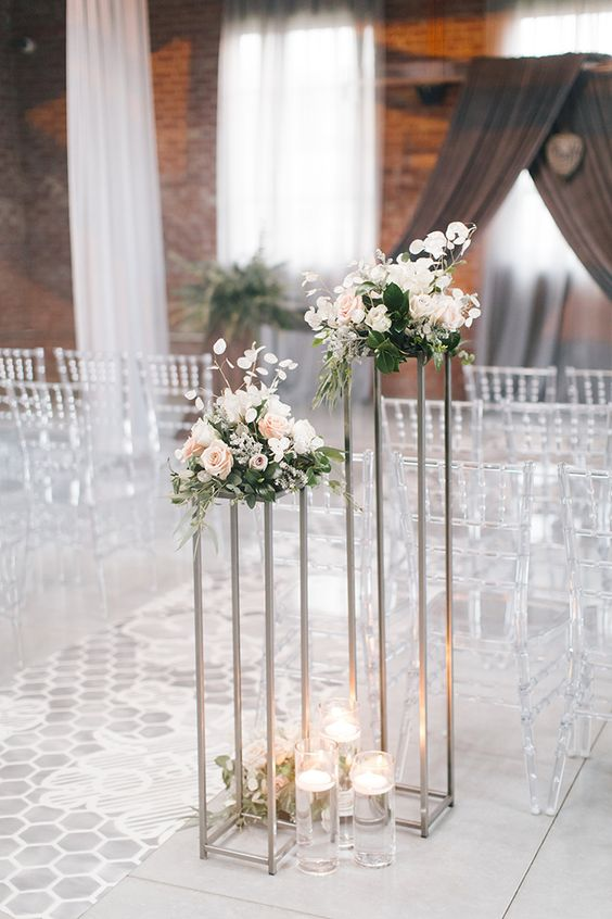 clear chairs with vintage design, a printed runner and florals on tall stands plus floating candles down for a romantic meets modern look