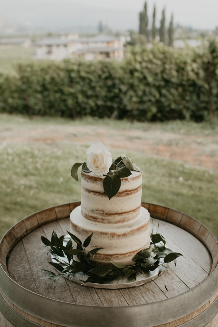 The wedding cake was a naked one, decorated with greenery and topped with a single white bloom