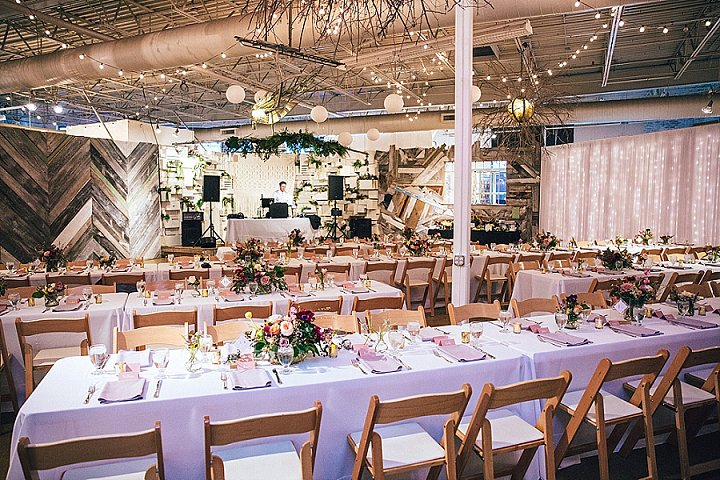 The wedding reception space featured many lights, branches and bright floral centerpieces