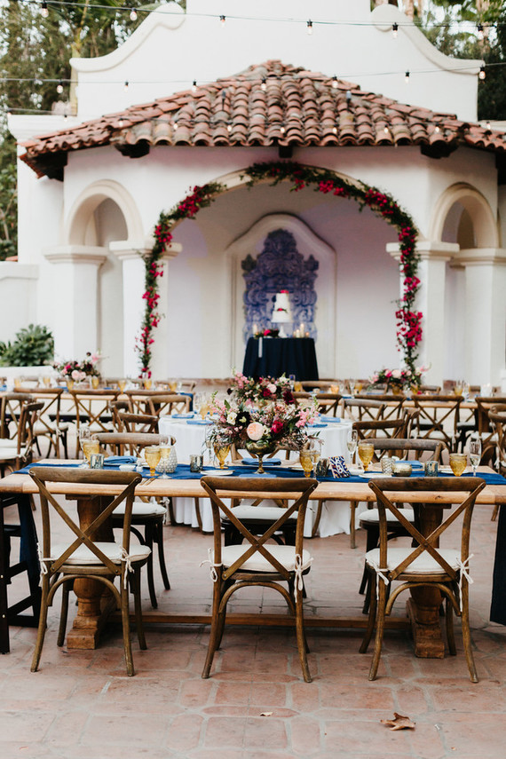 The wedding reception was done with uncovered wooden tables and elegant cjairs, navy runners and amber glasses