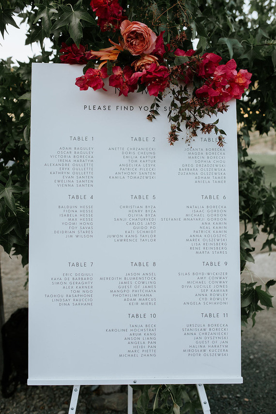 The wedding seating chart was done in modern style and topped with red blooms