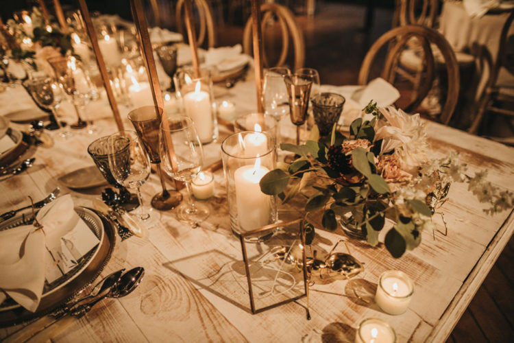 The wedding table setting was done with candles, greenery, elegant cutlery and chargers