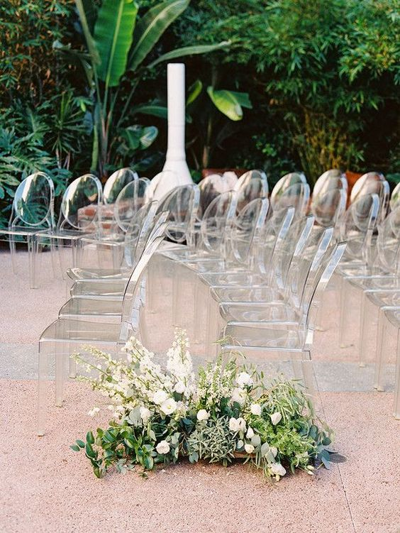 clear ghost chairs and a lush greenery and white bloom arrangement for a beautiful modern outdoor wedding aisle