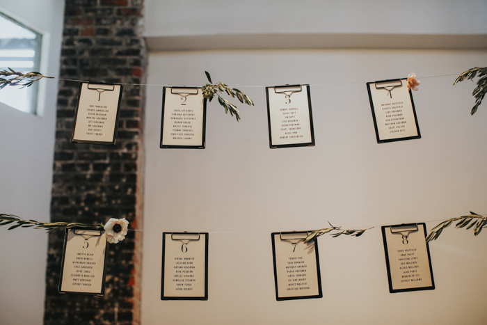 The seating chart was suspended in the air and decorated with blooms and greneery