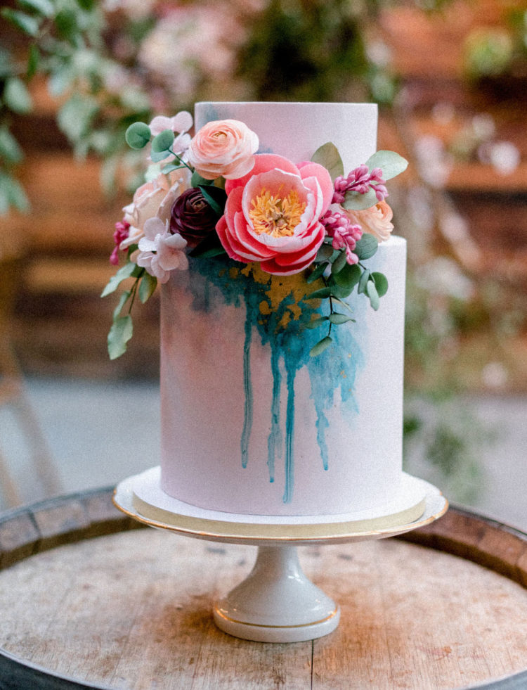 The wedding cake combined pink and teal and lush fresh blooms