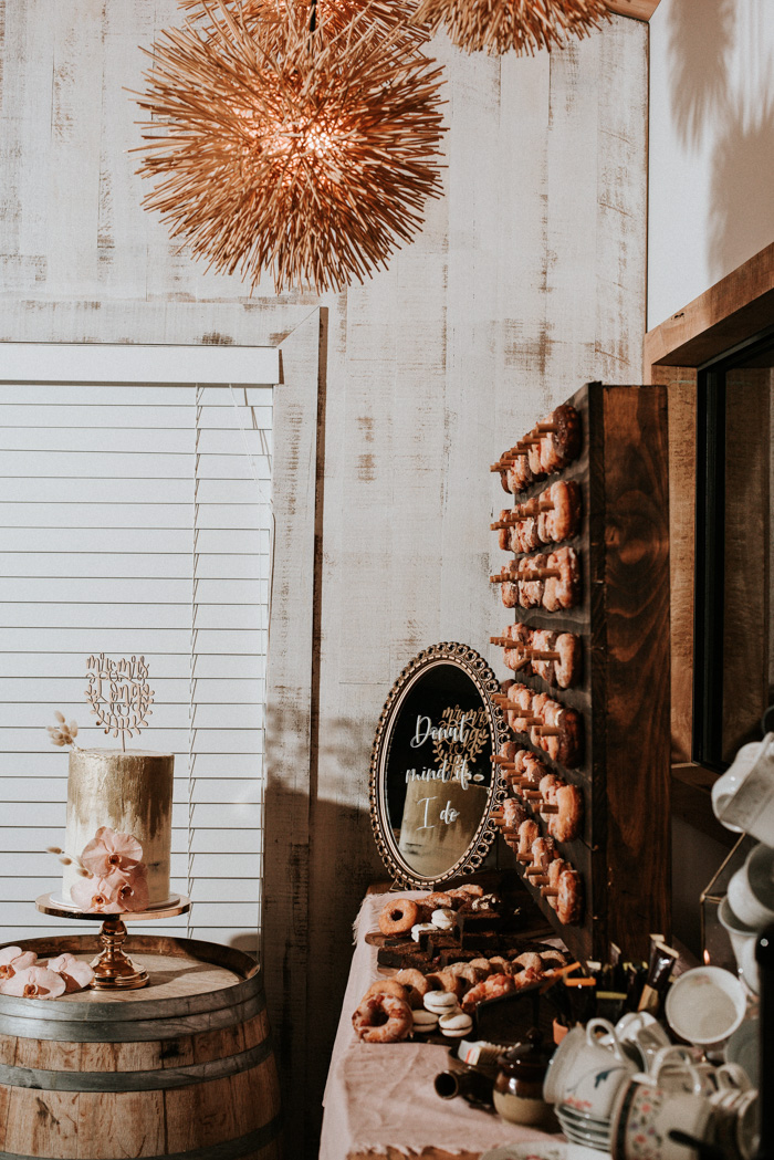 The wedding dessert table was done with a trendy donut wall and lots of donuts and macarons