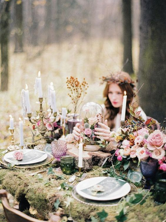 a romantic enchanted forest wedding table with moss, foliage, pink blooms, dried herbs and lots of candles