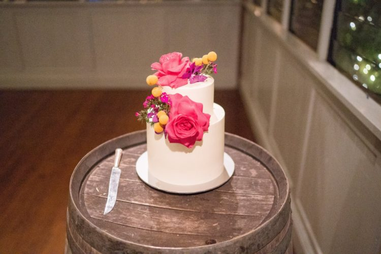 The wedding cake was a pure white one, topped with fuchsia blooms and billy balls
