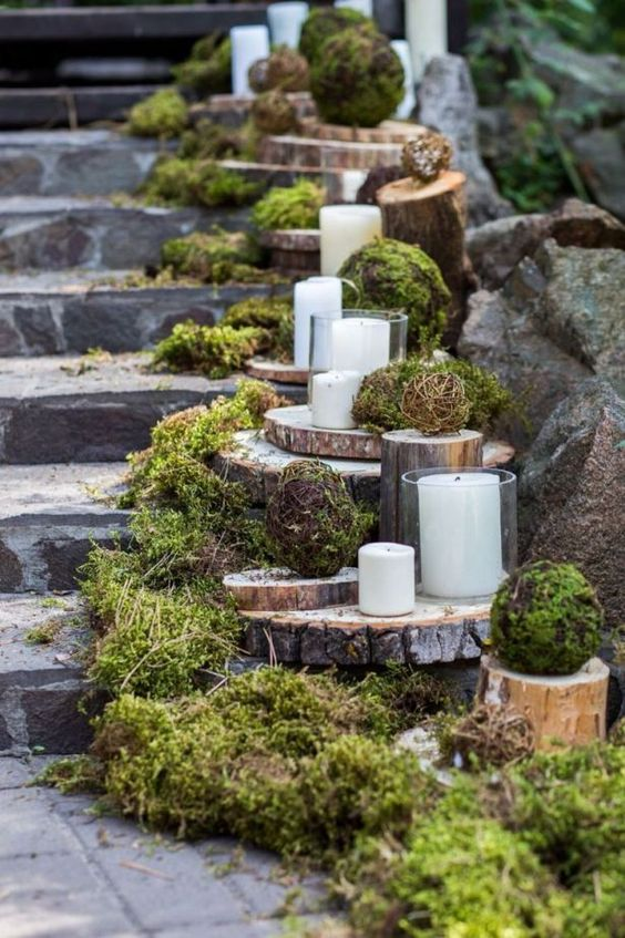 a staircase decorated with moss, wood slices, candles and moss balls looks super natural and beautiful