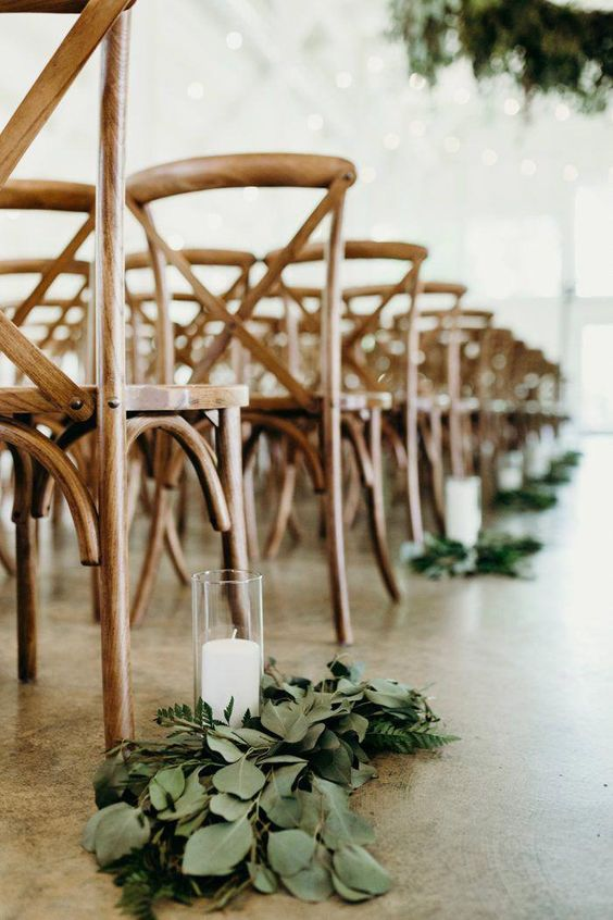 decorate your wedding aisle with fresh greenery and candles on the floor and add wooden chairs for a chic look