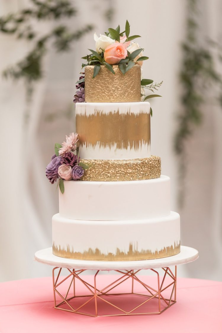 The wedding cake was done in white and gold, topped with fresh blooms and greenery plus a copper stand