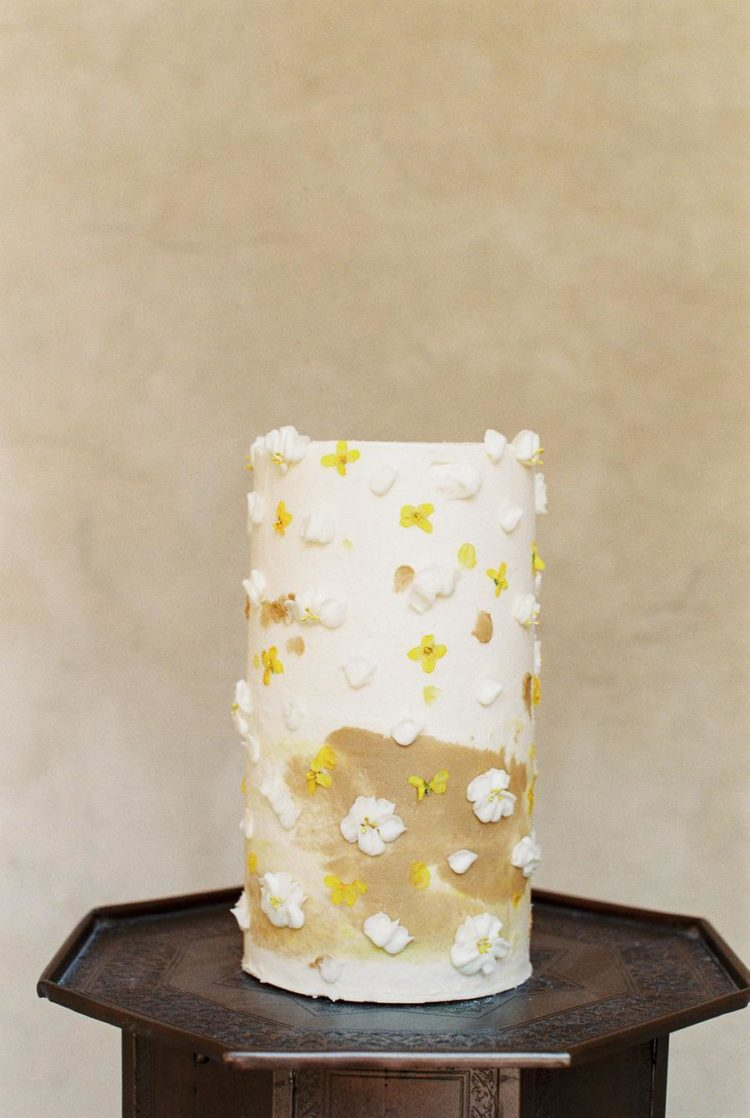 The wedding cake was tall, in white and mustard and with sugar blooms