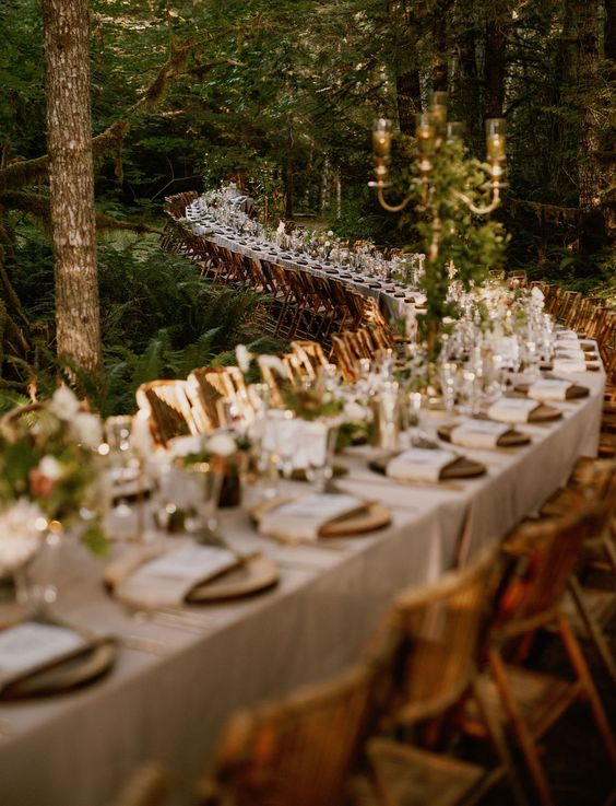 a super long curved wedding table with greenery and gold touches placed right in the forest is a fantastic idea