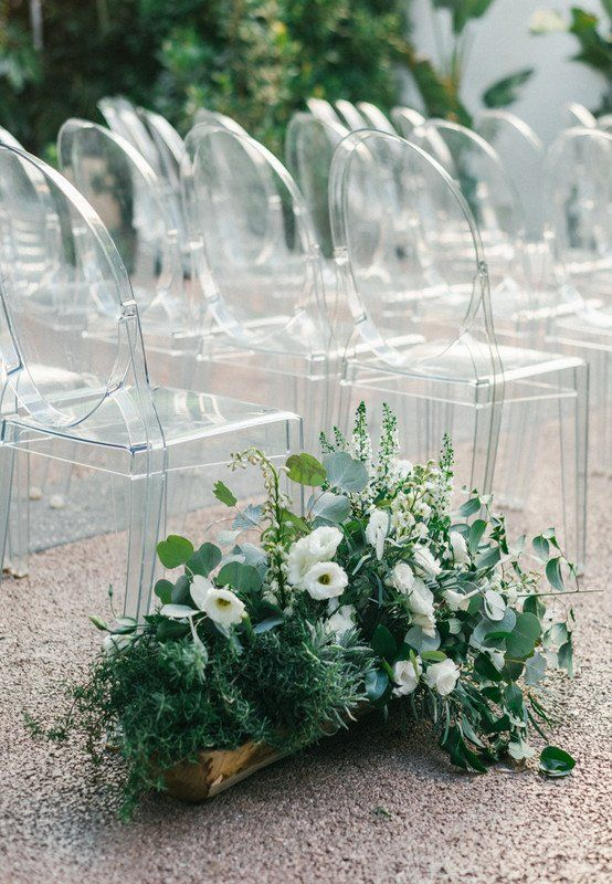 ghost chairs and a wooden planter with lush greenery and white blooms make up a gorgeous minimal wedding aisle